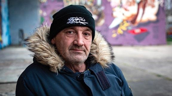 Älterer Mann mit schwarzer Mütze und Pelzkragenjacke.