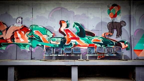Graffiti mit Buchstaben und einem  Faultier an einer Wand.