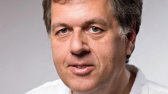 Frank Eckardt, ein Mann Mitte 50 mit weißem Hemd, schaut in die Kamera. Er ist Stadtforscher, derzeit an der Uni Weimar.