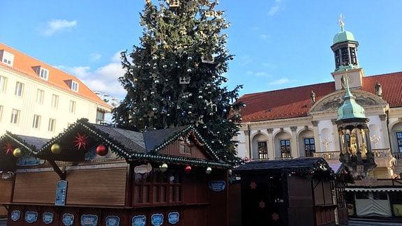 Geschmückter Baum zwischen Buden auf dem Magdeburger Weihnachtsmarkt.