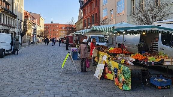 Frauen stehen an Obststand auf Wochenmarkt