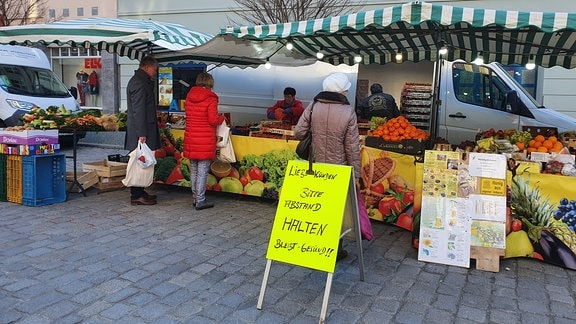 Kundschaft an Obststand auf Wochenmarkt, davor stehen Hinweisschilder