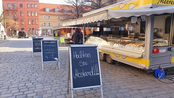 Hinweisschilder vor einem leeren Verkaufsstand auf einem Wochenmarkt