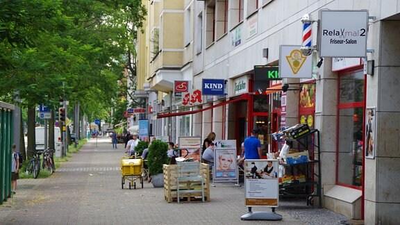 Blick die Lübecker Straße in der Neuen Neustadt herunter. Neben dem Fußweg: Viele bunte Ladenschilder von Friseuren, Apotheken, Bäckern, Banken, kleinen Gemüsemärkten und vielem mehr.