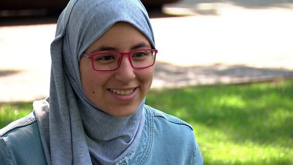 Ein Mädchen mit Kopftuch und Brille sitzt auf einer Wiese