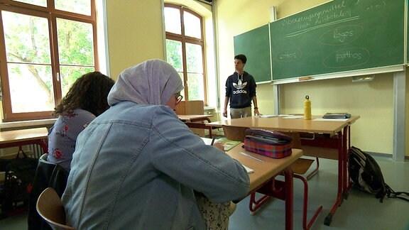Ein Mädchen mit Kopftuch sitzt in einem Klassenraum. Ein Jugendlicher steht vorn an der Tafel