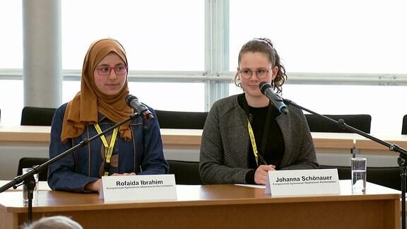 Zwei Mädchen stehen an einem Rednerpult