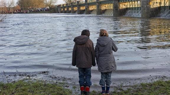 Zwei Mädchen beobachten 2011 das Steigen des Wasserstandes beim Öffnen des Wehres in Pretzien.