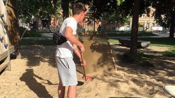 Ein Mann schaufelt Sand