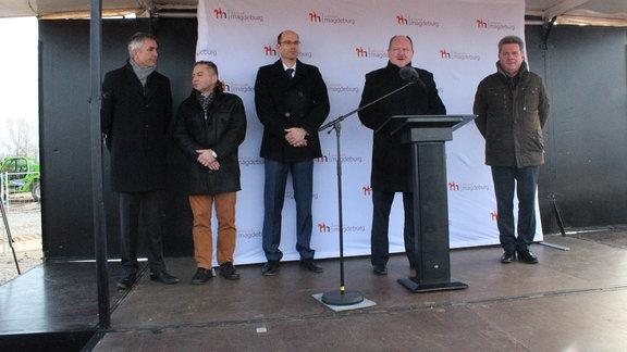 Fünf Männer auf einer Bühne, einer spricht am Mikrofon