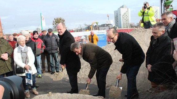 Drei Männer schippen Sand umringt von Menschen