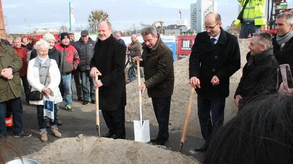 Drei Männer mit Späten vor einem Haufen Sand umringt von Menschen