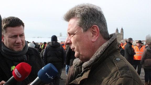 Grauhaariger Mann spricht in Mikrofone