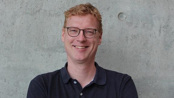 Ein großer Mann mit Locken und Brille steht vor einer Betonwand.