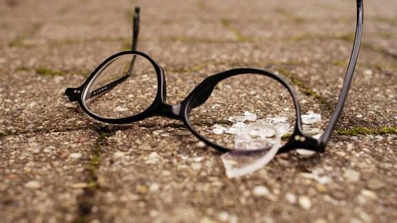 Zerbrochene Brille auf Straßenpflaster