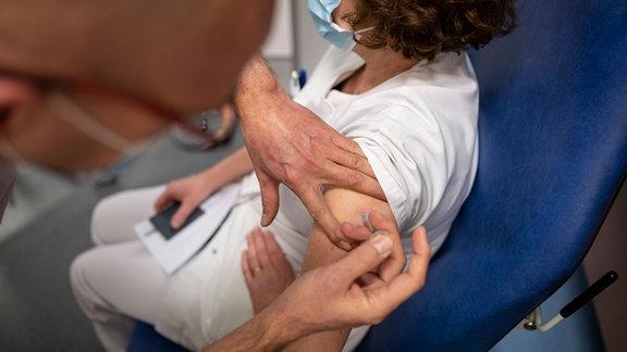 Eine Pflegekraft wird gegen Corona geimpft.