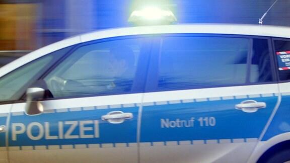 Einsatzwagen der Polizei mit eingeschaltetem Blaulicht, unterwegs.