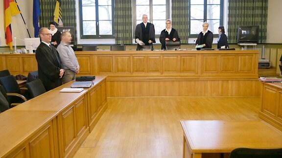 Menschen stehen bei der Begrüßung durch das Gericht.