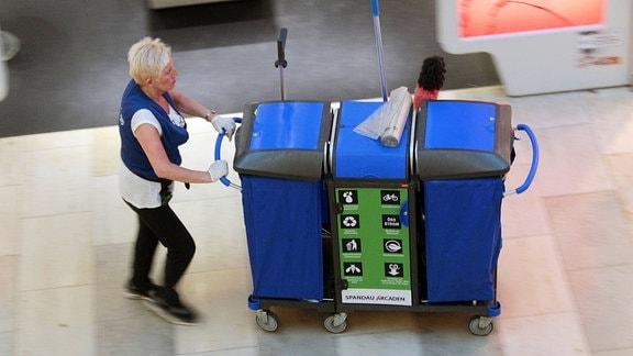 Reinigungskraft eines Service Unternehmens schiebt einen Wagen mit Reinigungsutensilien in einem Einkaufszentrum.
