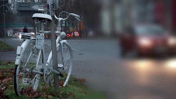 Ein weißes Fahrrad am Straßenrand