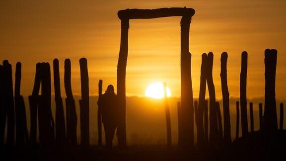 Ein Besucher des Ringheiligtums Pömmelte steht bei Sonnenuntergang an einem Tor der Anlage.