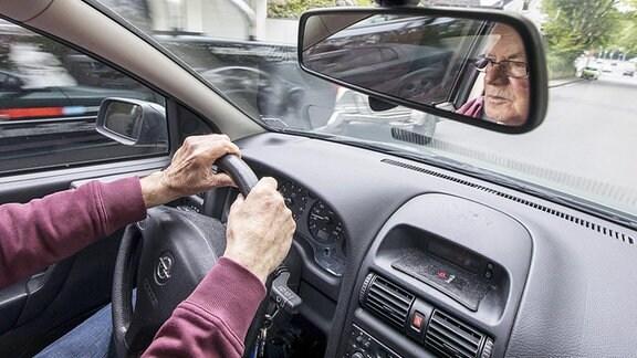 Ein älterer Herr fährt mit einem Wagen.