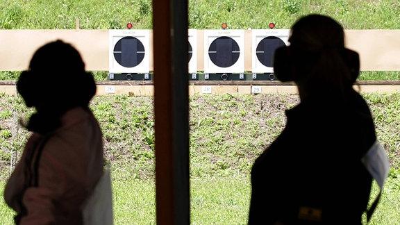 Die Silhouette zweier Schützen auf einem Schießstand