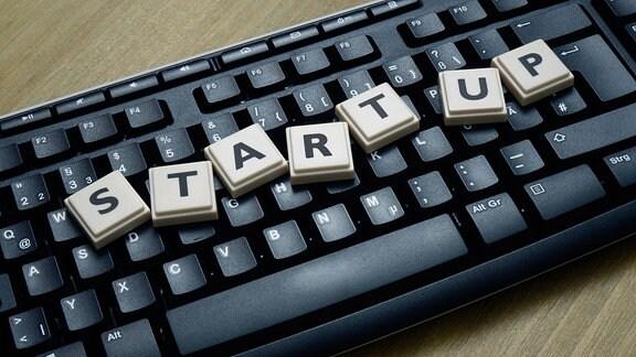 Auf einer Computertastatur liegt das Wort Start-up.