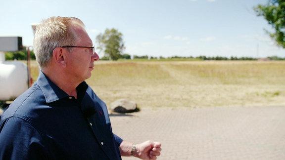 Profil eines Mannes, der neben einem Feld steht.