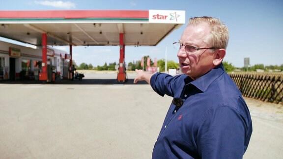 Ein Mann zeigt auf eine Tankstelle.