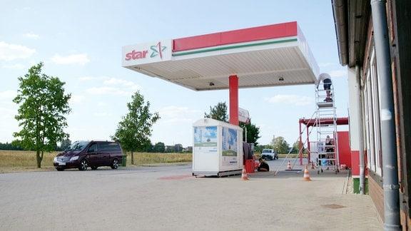 Eine Tankstelle neben einer Landstraße.