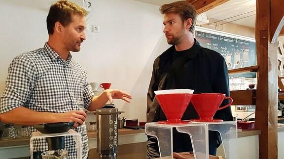 Zwei Männer hinter Filtergeräten, einer erklärt dem anderen etwas.