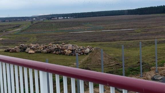 Blick von Brücke auf Felder, große Steine und eine Ortschaft