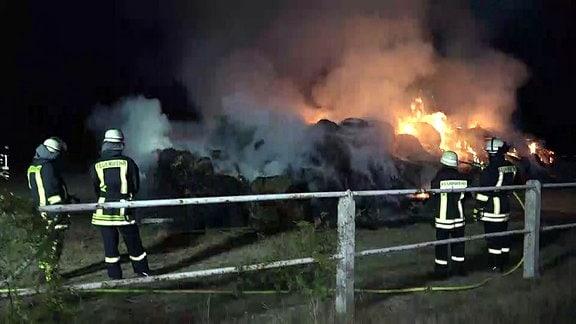 Feuerwehrmänner löschen die brennenden Strohballen in der Dunkelheit.