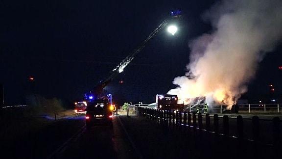 Die Feuerwehr löscht brennende Strohballen in der Dunkelheit.