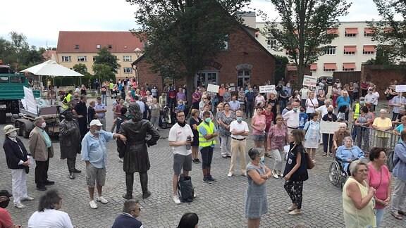 Demonstranten stehen mit einigen Schildern auf einem Platz in Havelberg.