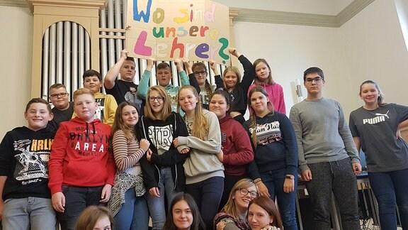 Schüler halten einen Banner in den Händen, auf dem steht: Wo sind unsere Lehrer?