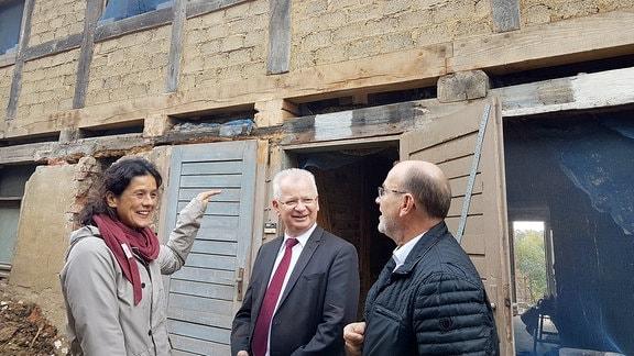 Eine Frau steht mit zwei Männern vor einem Fachwerkhaus und erklärt etwas.