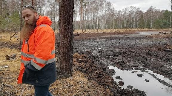 Mann in orangener Warnjacke steht in Wald mit Moor und dreht sich zur Seite
