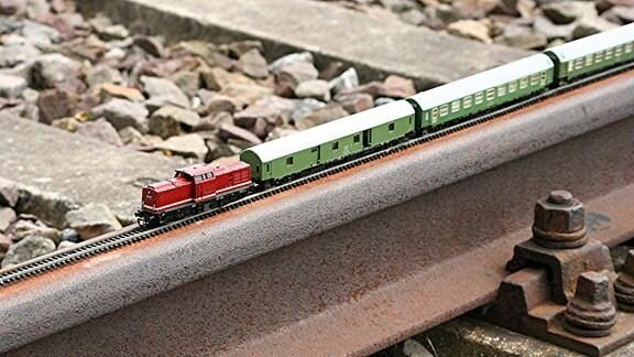 Symbolbild Kleinbahn - Eine Modellbahn steht auf einem großen Bahngleis.