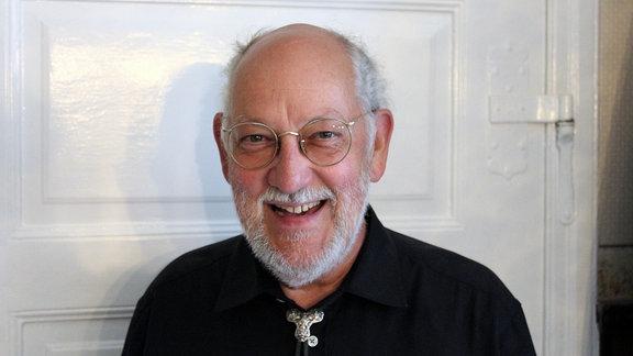 Ein Pfarrer steht vor einer weißen Tür und lächelt in die Kamera.