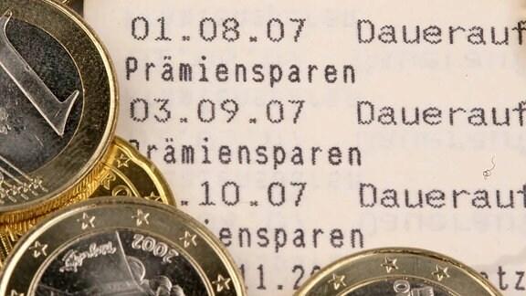 Euromünzen auf einem Sparbuch mit dem Schriftzug - Lösungswort.
