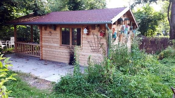 Laube aus Holz, außen mit bunten Vogelhäuschen und Brandspuren