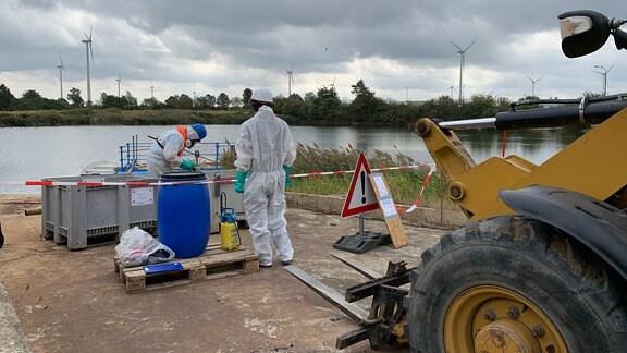 Kräfte in Schutzanzügen untersuchen die Giftschlammgrube in Brüchau.