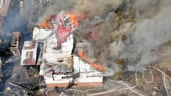 Blick von oben auf ein Einfamilienhaus in Flammen