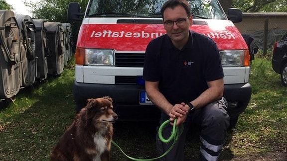 Mann kniet mit Hund vor Rettungswagen