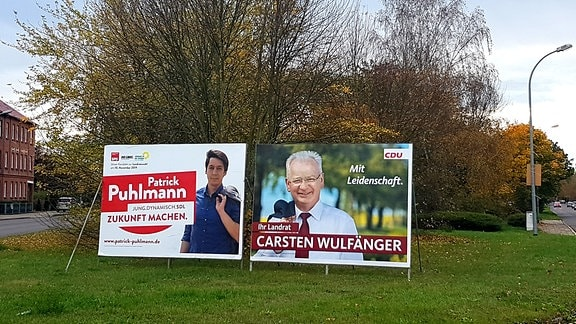 Zwei Schilder mit Wahlwerbung in einem Park in Stendal