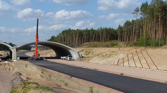 Kran an Brücke auf Autobahn-Baustelle