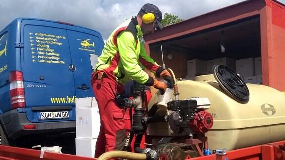 Mann in Schutzkleidung montiert Schlauch an Tank auf Lkw