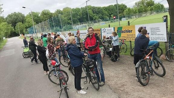 Leute stehen mit ihren Fahrrädern an einem Sportplatz.